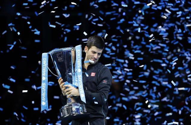 Novak Djokovic of Serbia prepares to lift the trophy after winning the final of the ATP World Tour Finals singles tennis match against Rafael Nadal of Spain at the O2 Arena in London Monday, Nov. 11, 2013. (AP Photo/Sang Tan)