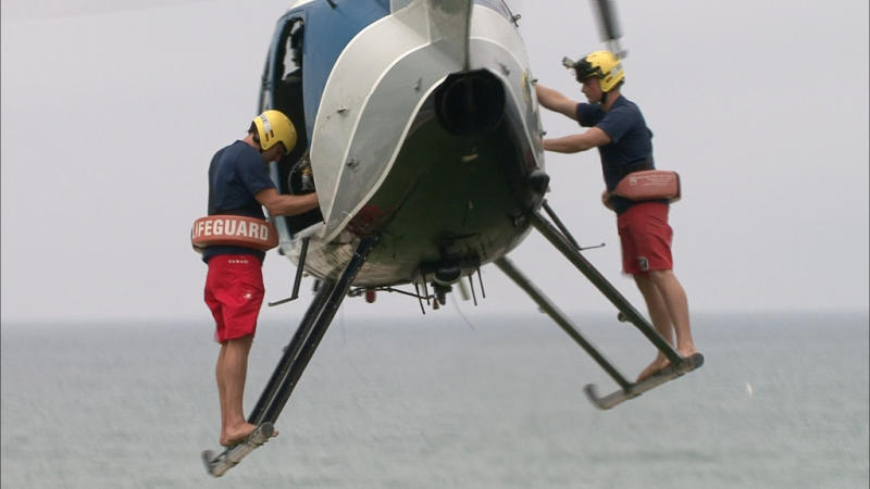 """In this undated image released by The Weather Channel, two lifeguards prepare to make a rescue in a scene from """"""""Lifeguard!,"""" about beach rescuers in southern California. The series airs Thursdays at 9 p.m. on The Weather Channel. The Weather Channel is in the midst of a transformation with original programming about Arctic pilots, steel workers, wind turbine and power line repairers and Coast Guard rescuers in both icy and tropical climates. (AP Photo/The Weather Channel)"""