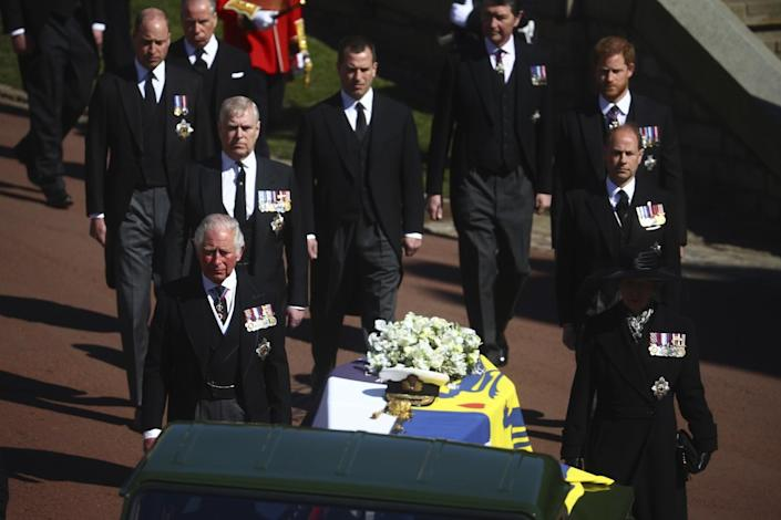 Members of the royal family walk behind the coffin of Prince Philip as it is driven at Windsor Castle.