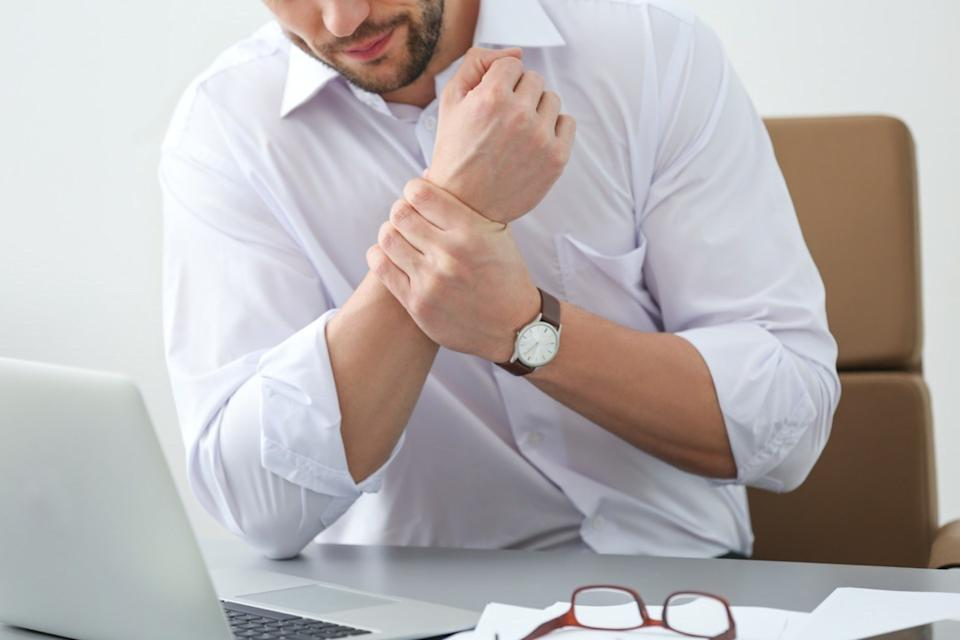 man suffering from wrist pain in office, closeup