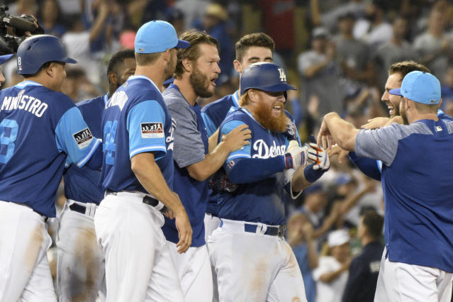 "<a class=""link rapid-noclick-resp"" href=""/mlb/teams/lad"" data-ylk=""slk:Los Angeles Dodgers"">Los Angeles Dodgers</a> mob <a class=""link rapid-noclick-resp"" href=""/mlb/players/8588/"" data-ylk=""slk:Justin Turner"">Justin Turner</a>, second from right, after hitting an RBI single in the twelfth inning of a baseball game to beat the <a class=""link rapid-noclick-resp"" href=""/mlb/teams/sdg"" data-ylk=""slk:San Diego Padres"">San Diego Padres</a> 5-4, Saturday, Aug. 25, 2018, in Los Angeles. (AP Photo/Michael Owen Baker)"