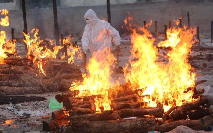 A social worker wearing PPE walks amid burning funeral pyres as he performs last rites of the Covid-19 victims in Bhopal - SANJEEV GUPTA/EPA-EFE/Shutterstock
