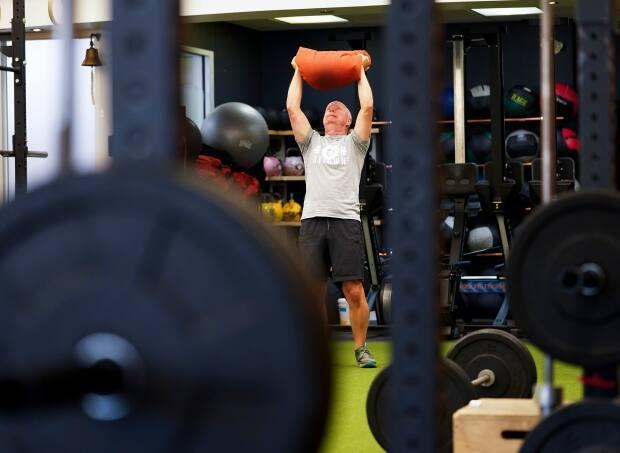 Paul Roberston works out at Crossfit Bytown as patrons return to the gym as Ontario enters Step 3 of reopening during the COVID-19 pandemic in Ottawa on Friday. (Sean Kilpatrick/The Canadian Press - image credit)