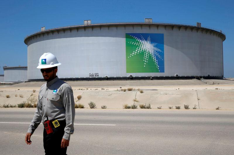 FILE PHOTO: An Aramco employee walks near an oil tank at Saudi Aramco's Ras Tanura oil refinery