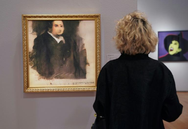 """A woman examines """"Portrait of Edmond Belamy"""" an AI work created by Obvious, which sold for $432,500 at Christie's in October 2018"""