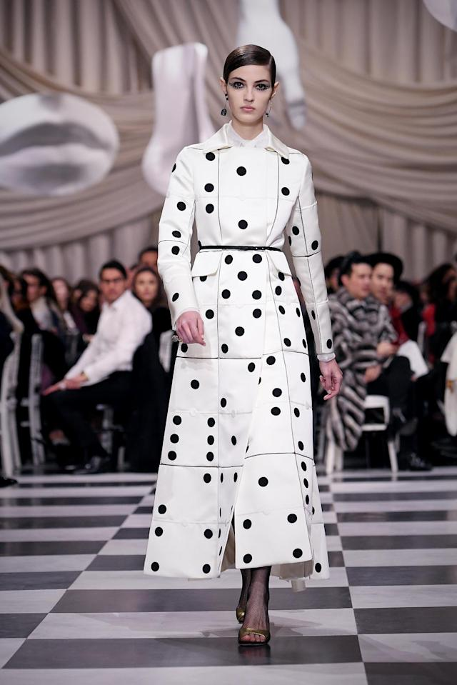 <p>A model wears a domino black and white themed trench coat from the Dior Haute Couture SS18 collection. (Photo: Getty) </p>