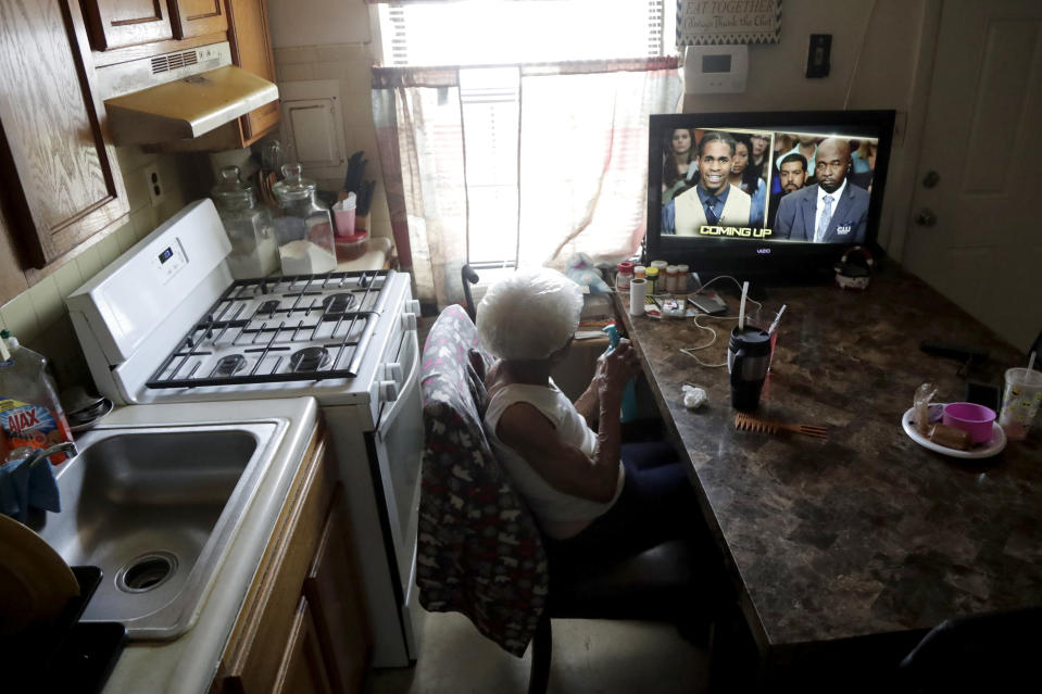 Carrie Newson watches television in the dining area inside her home at the Dutch Village apartments, Tuesday, July 30, 2019, in Baltimore. Newson has complained to management about mice and mold in her home but the issues have yet to be fixed. The apartment complex is owned by Jared Kushner, son-in-law of President Donald Trump. (AP Photo/Julio Cortez)
