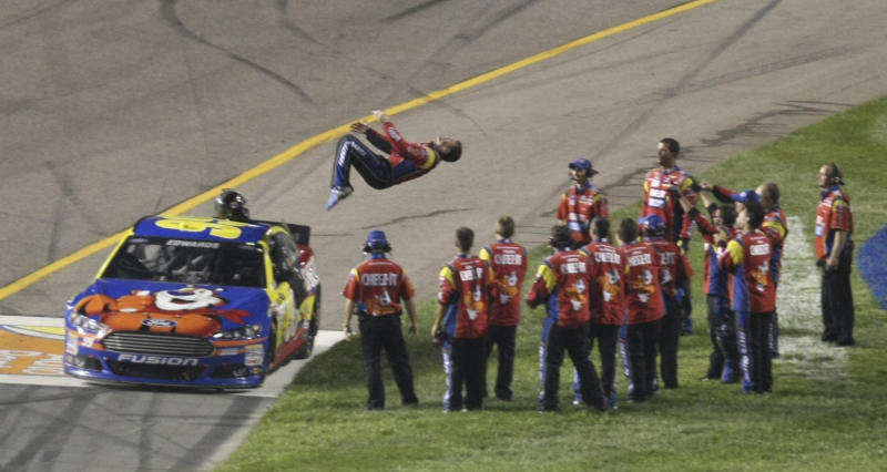 Carl Edwards does a backflip as team members watch after he won the NASCAR Sprint Cup Series auto race at Richmond International Raceway in Richmond, Va., Saturday, Sept. 7, 2013. (AP Photo/Jason Hirschfeld)