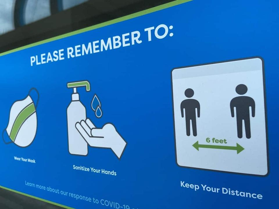 A sign encourages patrons of a business to wear masks, sanitize hands and keep their distance from others.  (CBC - image credit)