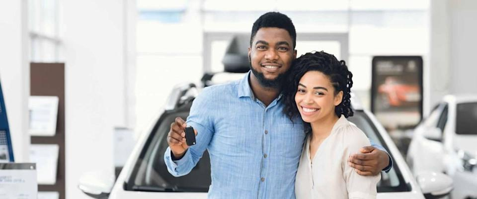 Happy couple standing holding a key in front of a white car at a dealership.