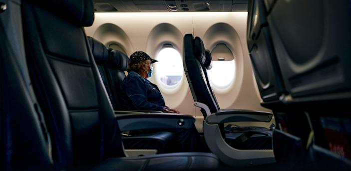 Traveler on a plane wearing a mask during the pandemic.