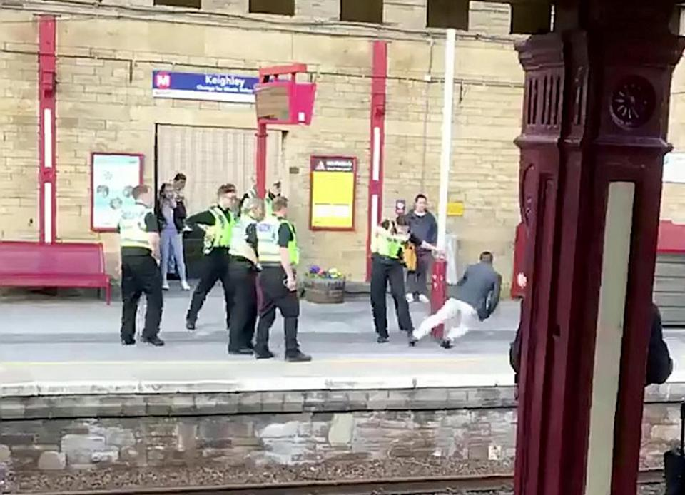 <em>The footage shows police surrounding the man before firing the taser (Picture: SWNS)</em>