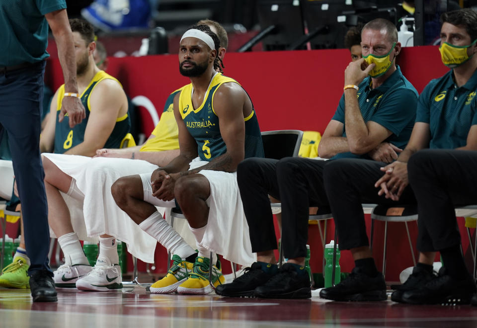Australia's Patty Mills (5), center, reacts after their loss in the men's basketball semifinal game against the United States at the 2020 Summer Olympics, Thursday, Aug. 5, 2021, in Saitama, Japan. (AP Photo/Charlie Neibergall)
