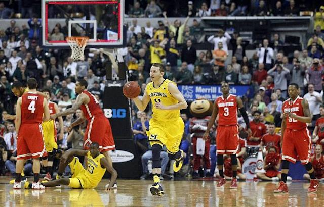 Michigan guard Nik Stauskas (11) takes off with the ball as the time runs out of the game against Ohio State in the second half of an NCAA college basketball game in the semifinals of the Big Ten Conference tournament Saturday, March 15, 2014, in Indianapolis. Michigan won 72-69. (AP Photo/Kiichiro Sato)
