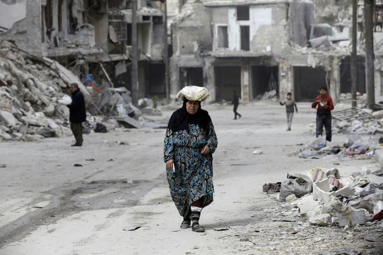 A woman walks up a street lined with heavily-damaged buildings in former rebel-held district of Shaar that Syrian government forces recaptured in December, in picture taken on March 9