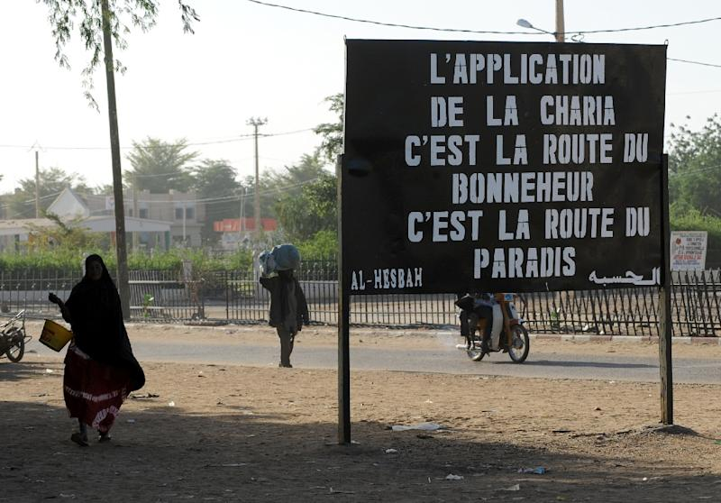 "Malians walk past a billboard left by the MUJAO, an offshoot of Al Qaeda in the Islamic Maghreb, on January 30, 2013, reading ""Enforcing Sharia is the road to happiness, it is the road to paradise,"" in the northern city of Gao"