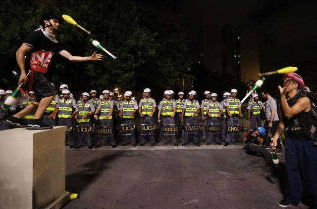 Demonstrators and jugglers perform in front of military policemen during a protest against the 2014 World Cup, in Sao Paulo March 13, 2014. An estimated 1,500 protesters gathered to march the streets of downtown Sao Paulo to show they are against the World Cup and against the costs associated with Brazil's hosting the sporting event. Activists are demanding more money be spent on education, health care, public transportation and to fight crime. REUTERS/Nacho Doce (BRAZIL - Tags: SPORT SOCCER WORLD CUP POLITICS CIVIL UNREST CRIME LAW)
