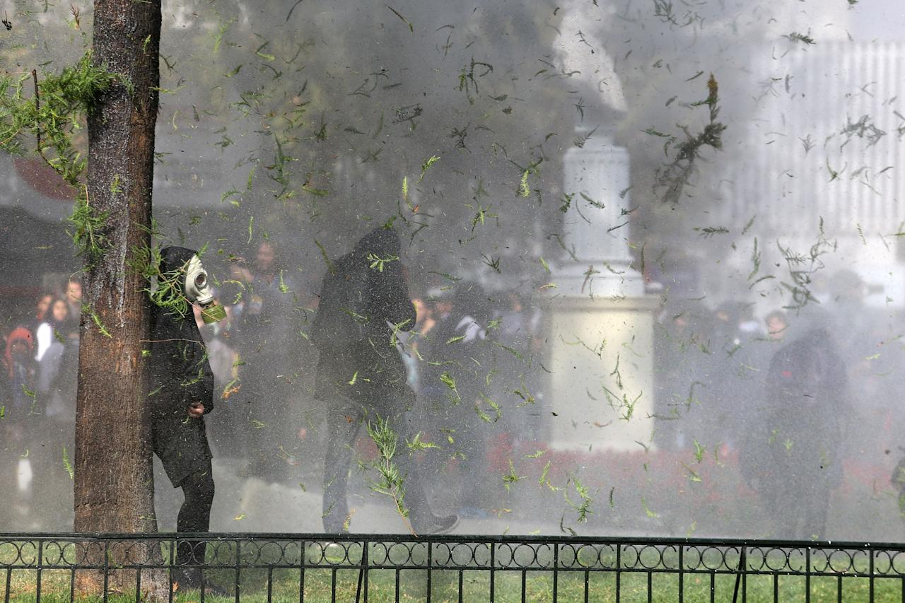 <p>Demonstrators take cover as they clash with riot police during a students' march for a better education reform in Santiago, Chile May 9, 2017. REUTERS/Ivan Alvarado </p>