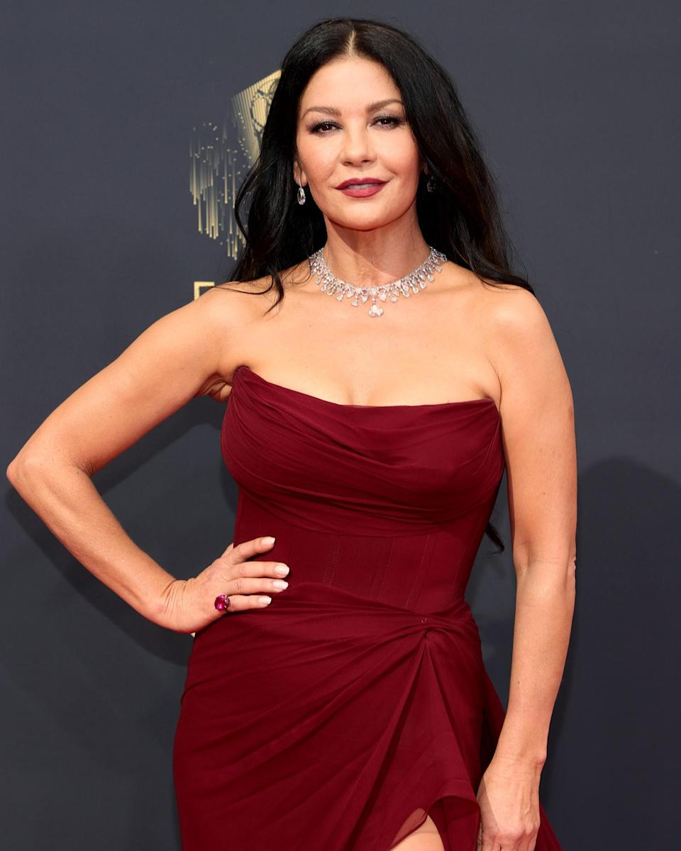 """<p>Catherine Zeta-Jones knows a thing or two about how to make an entrance on the red carpet, and she certainly didn't pipe down for this year's Emmys. Her smoky eye makeup and red wine lip was created using products from her beauty line <a href=""""https://www.wunder2.com/collections/casa-zeta-jones"""" rel=""""sponsored noopener"""" target=""""_blank"""" data-ylk=""""slk:Casa Zeta-Jones"""" class=""""link rapid-noclick-resp"""">Casa Zeta-Jones</a>. As for hair, the star added in some soft waves and kept her long locks tucked behind her shoulders. </p>"""