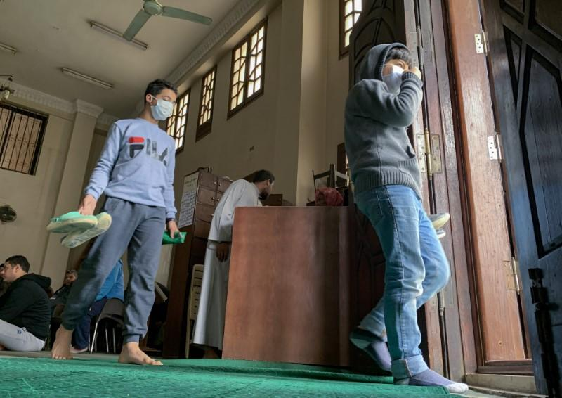 Boys wear protective masks, as means of prevention against the coronavirus disease (COVID-19) at the Al Rahman mosque, walk after Friday prayers inside Abdel Rahman Mosque in the Cairo neighborhood of Maadi