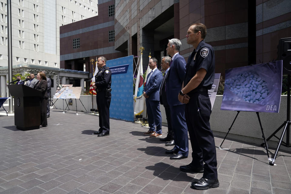 Officials stand behind Acting United States Attorney Tracy Wilkison, far left at podium, outside the Edward R. Roybal Federal Building, Thursday, May 13, 2021, in Los Angeles. Federal authorities say they have arrested at least 10 suspected drug dealers accused of selling fentanyl and other opioids that led to overdose deaths. (AP Photo/Marcio Jose Sanchez)