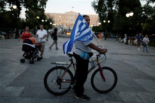 A New Democracy conservative party supporter holds a greek flag next a New Democracy party election kiosk at Syntagma square in Athens, Sunday, June 17, 2012. The pro-bailout New Democracy party came in first Sunday in Greece's national election, and its leader has proposed forming a pro-euro coalition government.(AP Photo/Petros Giannakouris)