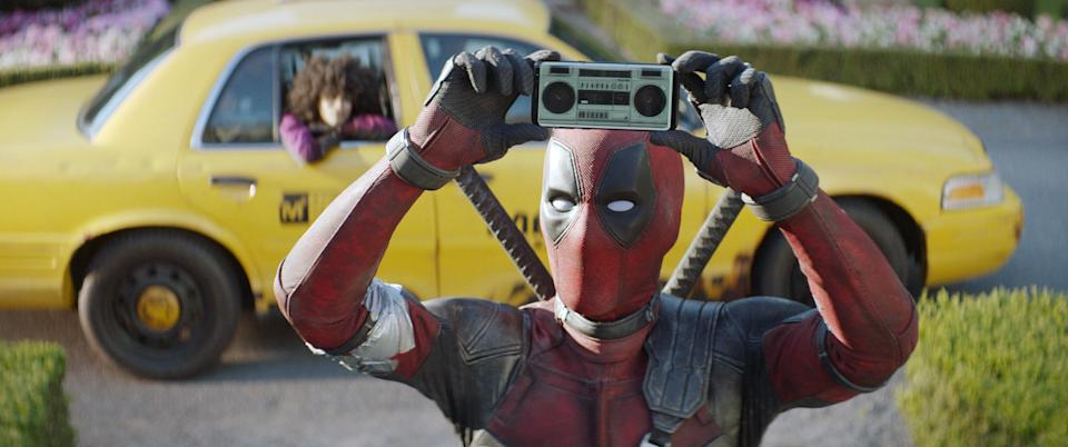 deadpool holding up a small tape deck playing music while a cab waits behind