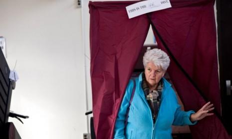 A woman exits a voting booth at Silver Bay Elementary School on Election Day in Toms River, N.J. As the day drags on, more people will be clamoring for clues to the election's outcome, but they should be wary of exit polls.