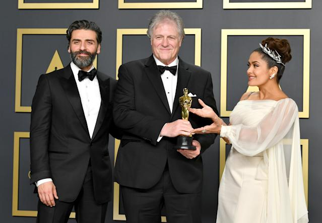 """Sound engineer Donald Sylvester, winner of the Sound Editing award for """"Ford v Ferrari,"""" poses with Oscar Isaac and Salma Hayek in the press room during the 92nd Annual Academy Awards at Hollywood and Highland on February 09, 2020 in Hollywood, California. (Photo by Amy Sussman/Getty Images)"""
