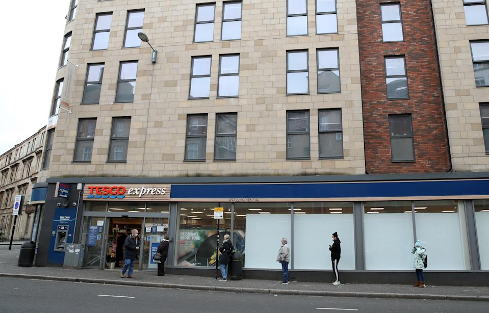 People follow social distancing guidelines as they queue outside a Tesco Express in Glasgow as the UK continues in lockdown to help curb the spread of the coronavirus.