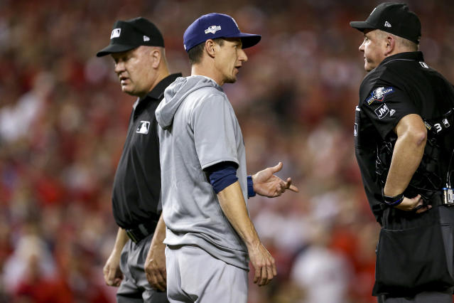 Milwaukee Brewers manager Craig Counsell, center, speaks to officials during the eighth inning of a National League wild-card baseball game against the Washington Nationals at Nationals Park, Tuesday, Oct. 1, 2019, in Washington. (AP Photo/Andrew Harnik)