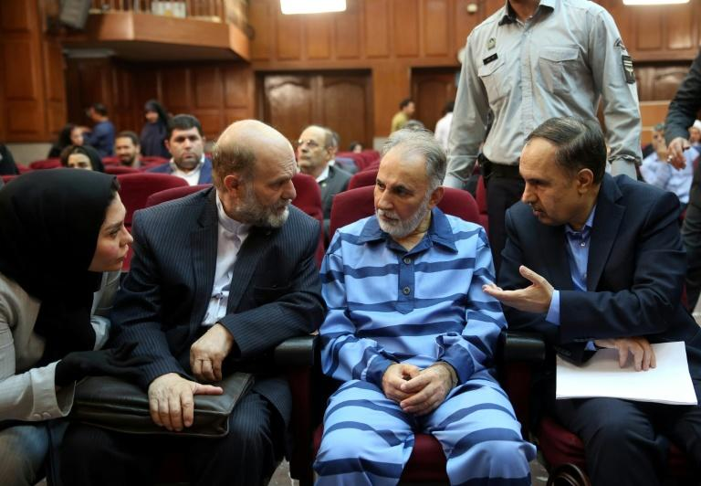 Former Tehran mayor Mohammad Ali Najafi (2nd-R), convicted of shooting his second wife, speaks with his lawyer at Iran's criminal court