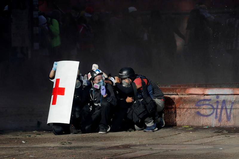 Members of a first aid team and a photographer take cover during an anti-government protest in Santiago, Chile on Oct. 28, 2019. (Photo: Henry Romero/Reuters)