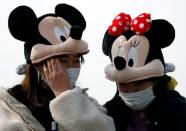 Visitors wearing protective face masks and Mickey and Minnie Mouse costumes, following an outbreak of the coronavirus, are seen outside Tokyo Disneyland in Urayasu