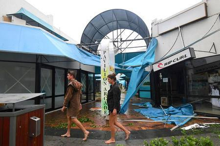 People walk past damaged shops after Cyclone Debbie hit the northern Queensland town of Airlie Beach, located south of Townsville in Australia