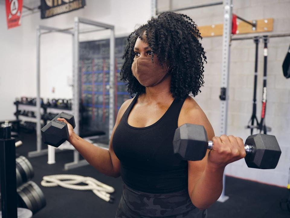 A woman working with a weightlifting equipment in a gym, while wearing a face mask.