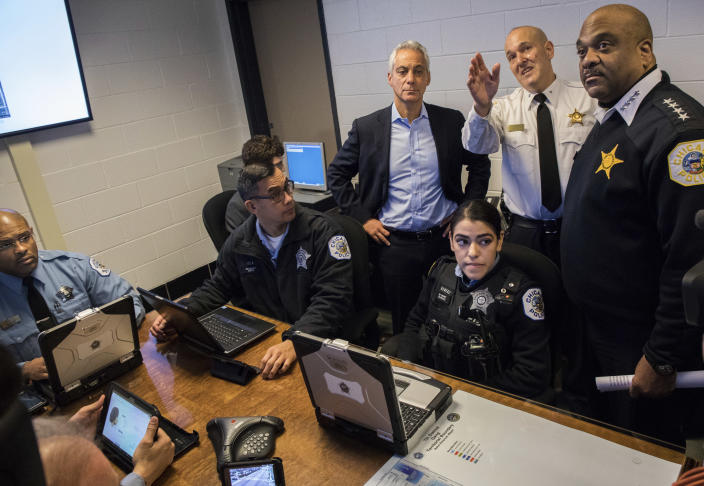 "FILE - In this Friday Jan. 27, 2017 file photo, Jonathan Lewin, center, deputy chief of the Chicago Police Department's technology and records group explains the program to Chicago police Superintendent Eddie Johnson, right, and Mayor Rahm Emanuel at Englewood station before announcing use of Shotspotter gunshot detection technology as part of a pilot project at Chicago's Harrison and Englewood district. In a Monday, May 3, 2021 court filing, community groups argue the gunshot detection system routinely reports gunshots where there are none, sending officers into predominantly Black and Latino neighborhoods for ""unnecessary and hostile"" encounters. (Zbigniew Bzdak/Chicago Tribune via AP)"
