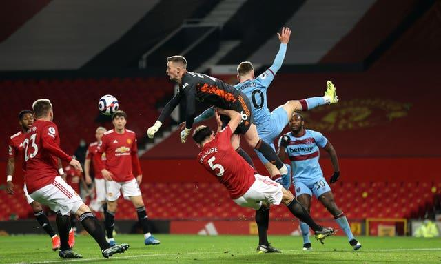 Dean Henderson, centre, punches clear under pressure from Jarrod Bowen, second right
