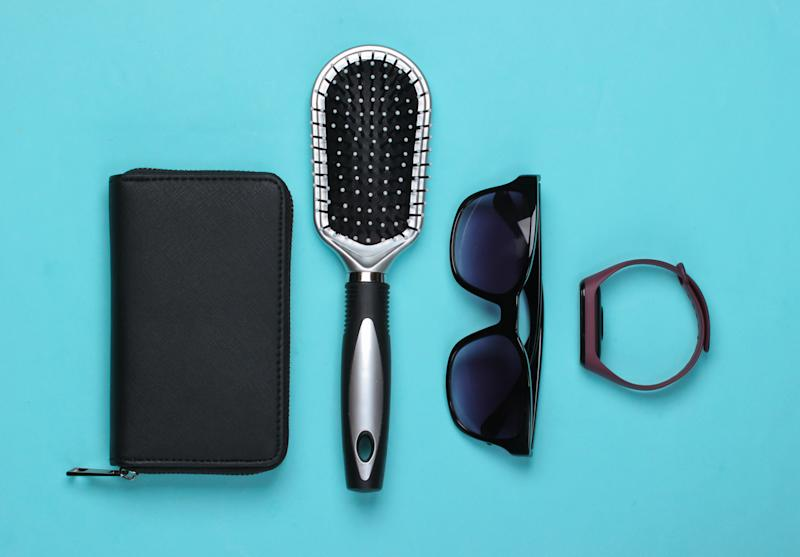 Wallet with sunglasses, hairbrush on blue pastel background. Women's accessories. Top view