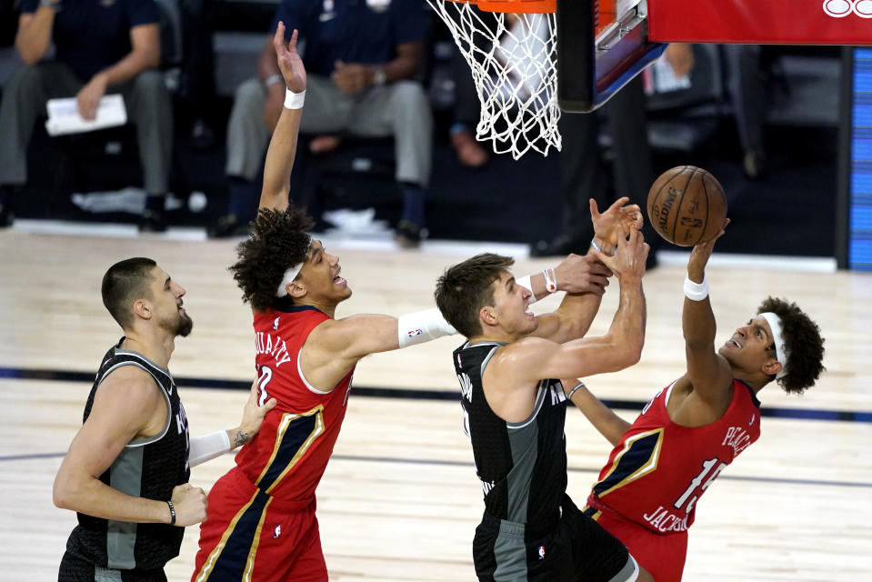 Sacramento Kings' Bogdan Bogdanovic, center right, competes for an offensive rebound against New Orleans Pelicans' Frank Jackson, right, and Pelicans' Jaxson Hayes, center left, as Kings' Alex Len, left, looks on during the second half of an NBA basketball game Thursday, Aug. 6, 2020 in Lake Buena Vista, Fla. (AP Photo/Ashley Landis, Pool)