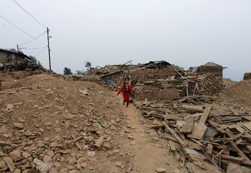 A child runs near a demolished earthquake-damaged home in Dolakha as hundreds of thousands of Nepali earthquake survivors still languish in temporary shelters one year after the disaster (AFP Photo/Prakash Mathema)