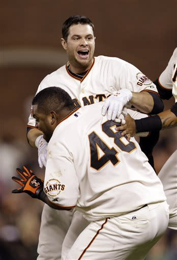 San Francisco Giants' Brandon Belt, top, is hugged by teammate Pablo Sandoval (48) after Belt drove in the game-winning run against the Arizona Diamondbacks in the bottom of the ninth inning of a baseball game on Monday, April 22, 2013 in San Francisco. (AP Photo/Marcio Jose Sanchez)