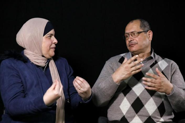 Nafez al-Damiri, a deaf and mute man who lost his right eye, speaks in sign language with his wife during a photo session in Jerusalem (AFP Photo/EMMANUEL DUNAND)