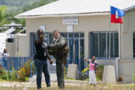 """U.S. Marine Cpl. Jacob Simons, right, coordinates the unloading of the food from a VM-22 Osprey with a Haitian aid worker at Jeremie Airport, Saturday, Aug. 28, 2021, in Jeremie, Haiti. The VMM-266, """"Fighting Griffins,"""" from Marine Corps Air Station New River, from Jacksonville, N.C., are flying in support of Joint Task Force Haiti after a 7.2 magnitude earthquake on Aug. 22, caused heavy damage to the country. (AP Photo/Alex Brandon)"""