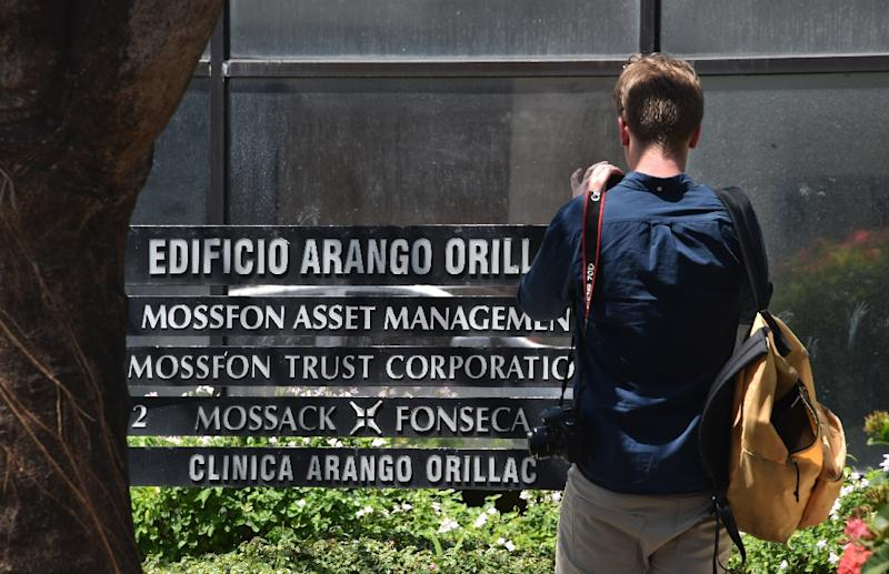 A journalist takes pictures of the facade of the building where Mossack Fonseca law firm offices are located in Panama City, on April 5, 2016 (AFP Photo/Rodrigo Arangua)