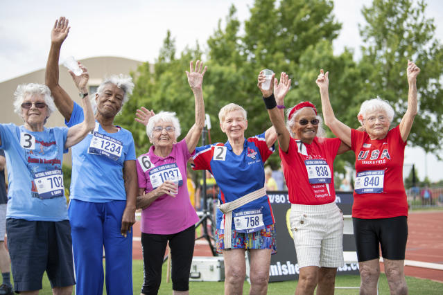 In this photo provided by the National Senior Games Association, competitors in the 90+ age division, including 103-year-old Julia Hawkins, of Baton Rouge, La., far right, wave to the crowd after their 50-meter race at the 2019 National Senior Games in Albuquerque, N.M., Monday, June 17, 2019. (Brit Huckabay/NSGA via AP)