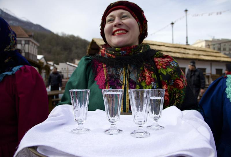 FILE - In this Feb. 6, 2013, file photo, a woman in a traditional folk costume welcomes guests with a beverage at a street in Rosa Khutor, some 60 km east of the Black Sea resort of Sochi, Russia. Sochi has long been a choice destination for Russia's political elite. Joseph Stalin's summer residence in Zeleni Mys even features a wax mannequin of the dictator at his desk. (AP Photo/Ivan Sekretarev, file)