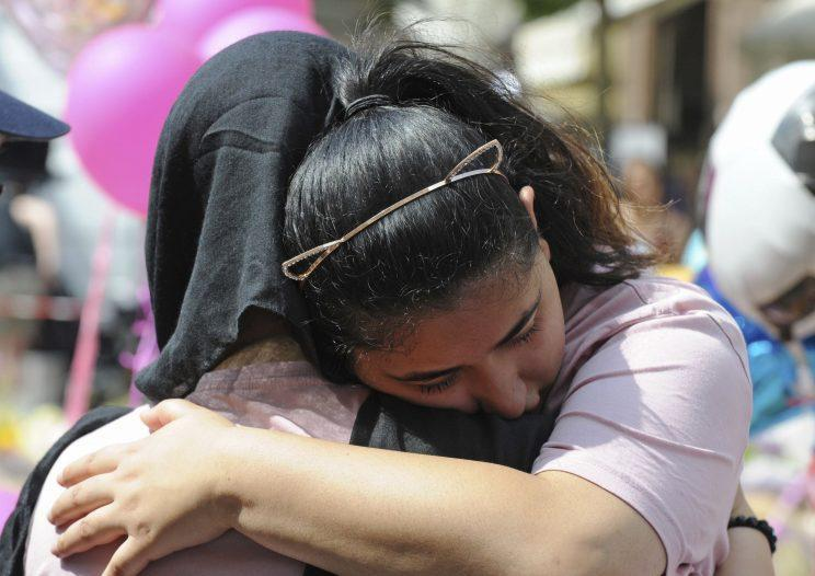 People comfort each other amid the tributes to the victims (Rex)