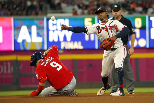 Atlanta Braves second baseman Ozzie Albies (1) throws to first to complete the double play after forcing out Washington Nationals' Brian Dozier (9) on a Kurt Suzuki ground ball in the fourth inning of a baseball game Saturday, July 20, 2019, in Atlanta. (AP Photo/John Bazemore)