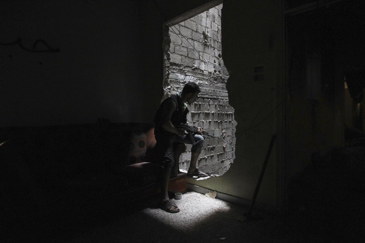 A member of the Shohadaa Badr Brigade, which operates under the Free Syrian Army, looks through a hole in the wall in Ashrafieh, Aleppo September 17, 2013. REUTERS/Muzaffar Salman (SYRIA - Tags: POLITICS CIVIL UNREST CONFLICT TPX IMAGES OF THE DAY)